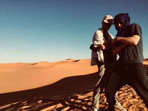 Two boys stand in the desert of Merzouga Morocco. One has a traditional scarf around his head and the other is wearing a hat and has a black vegetable tanned Moroccan leather bumbag around his body. They are surrounded completely by desert