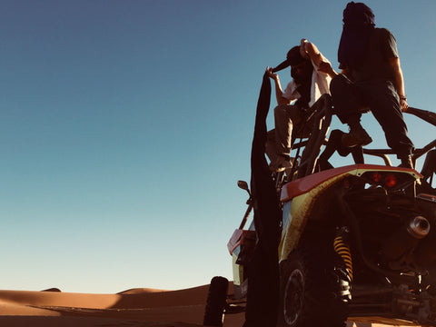 two men sit on top of their dune buggy in the desert. They are in Merzouga, Morocco. One is putting a traditional berber headscarf on as the tail end drapes all the way onto the floor. The other already has his face scarfed up. The sky is blue and the desert sand is orange