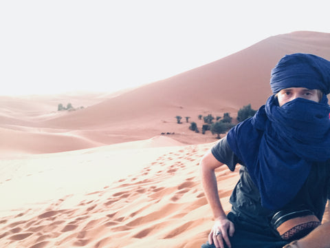 A boy sits in the desert wearing traditional berber head scarf to protect his face from the snd and the wind. Behind him the dunes are high, the sand s orange and the sky is blue, he is holding a vegetable tanned Moroccan leather bumbag with Moroccan Kilim carpet detailing