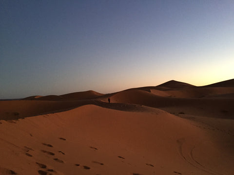 a man stands in the distance almost completely surrounded by desert orange sand dunes, the sky is a burnt colour, the sun is setting