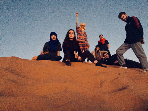 seven friends sit to take a picture completely surrounded by sand in the desert Merzouga Morocco. They area ll wearing different brightly coloured clothes with patterns and prints, they are also wearing Berber headscarves in bright colours