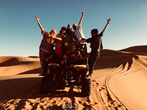 A group of friends both boys and girls are standing on and around their dune buggy in Sahara desert Merzouga Morocco. They are wearing bright patterns and print They are surrounded by the desert