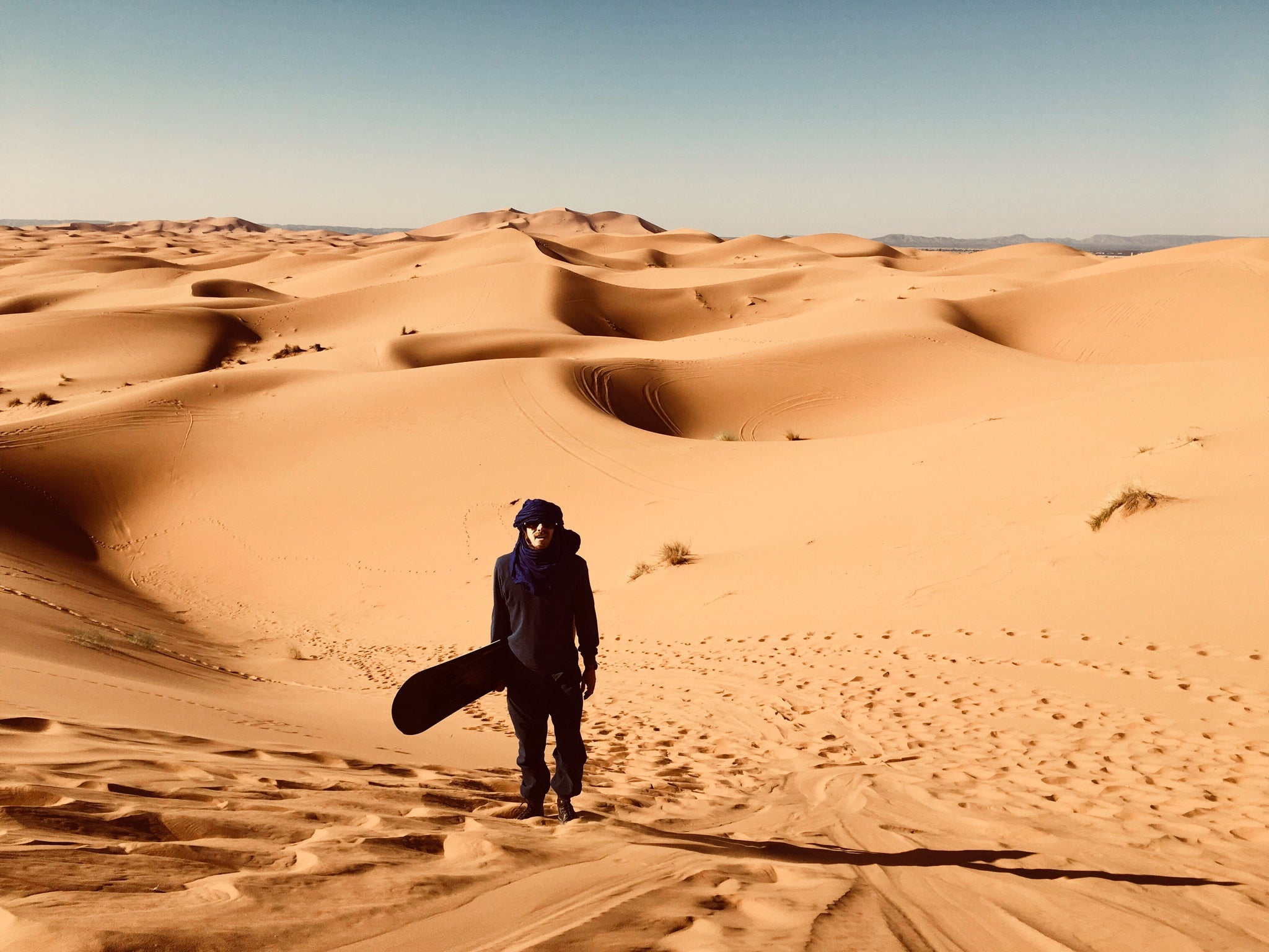 Boy sand boarding in the desert