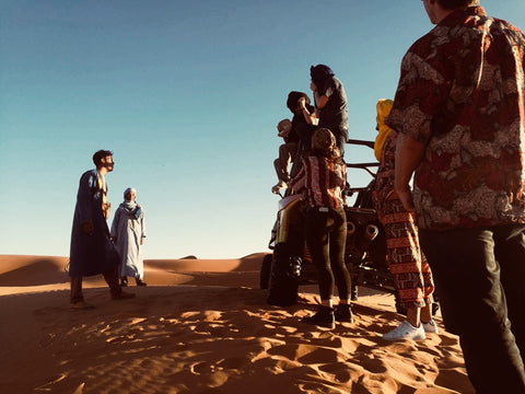 A group of friends stand on and arounds their dune buggy in the desert in Merzouga, Morocco. They are listening to the two local berber men explain to them the rules of the desert