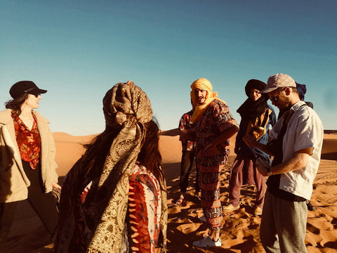 Friends are standing in the sahara desert with a local berber man, the sun is hot, the sand is bright orange and the sky blue. They are all wearing brightly coloured patterns and prints as well as bright coloured headscarves