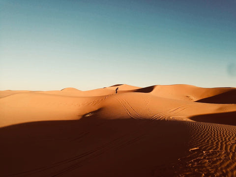 a man stands in the distance almost completely surrounded by desert orange sand dunes, the sky is blue. He is in Merzouga Morocco
