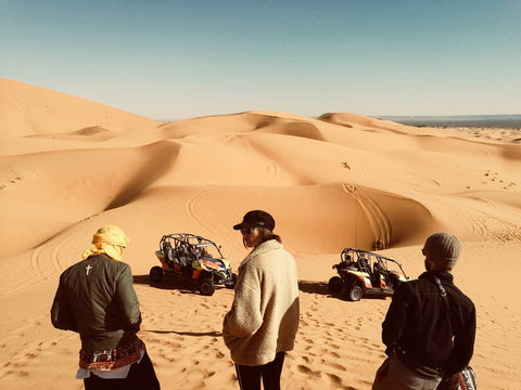 Three friends stand on a dune in the desert looking over the dune buggies that sit on their own in front of them. The sand in Merzouga, Morocco is bright orange and the sky is blue