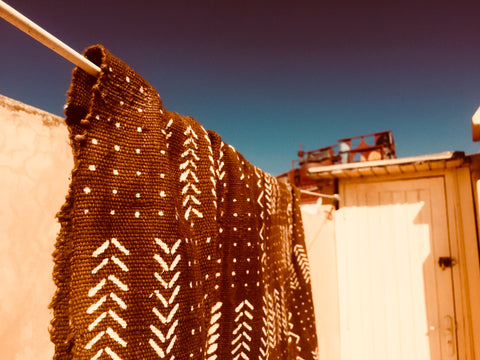 Mali Mud dyed blanket in brown colour hanging on a clothes line on a terrace in Essaouira Morocco