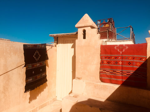Cactus silk berber rugs hanging on the walls of the roof terrace in Essaouira Morocco, the sun is shining it is a warm day and the sky is blue