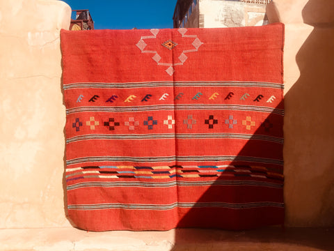 A red cactus silk berber rug is draped over the ledge of a roof terrace in Essaouira Morocco. The sun is shining and the sky is blue