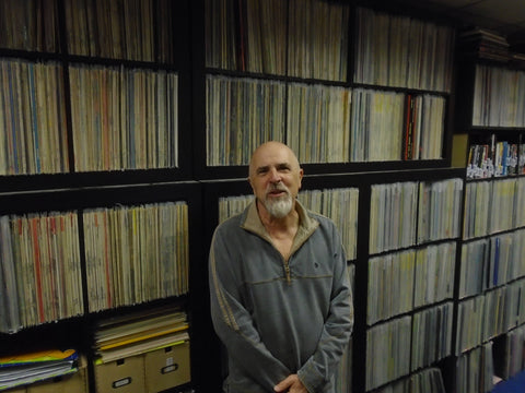 Mick Reynolds in front of a wall of vinyl