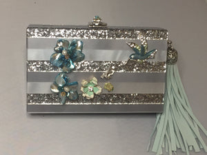 "Sparkly Gray Vintage Style Lucite Clutch With Hideaway Silver And Blue Cross-Body Chain; Adorned With Vintage Silver And Blue Enamel Flowers And Hummingbirds, Topped With Blue And Green Jeweled Clasp; Large Light Blue Suede Tassel. Dimensions - Height 5""; Length 7""; Depth 1.75""; Chain 26"""