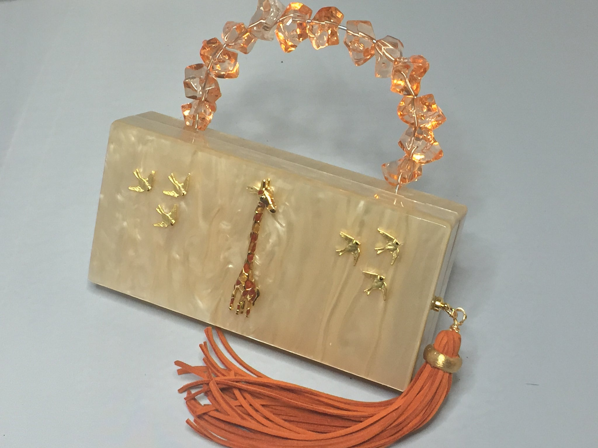 "Vintage Style Creamy Peach Lucite Rectangular Clutch With Hideaway Cross-Body Chain, Long Peachy Suede Tassel Adorned With Golden Giraffe And Golden Birds Dimensions - Height 5""; Width 7.5""; Depth 1.75"""