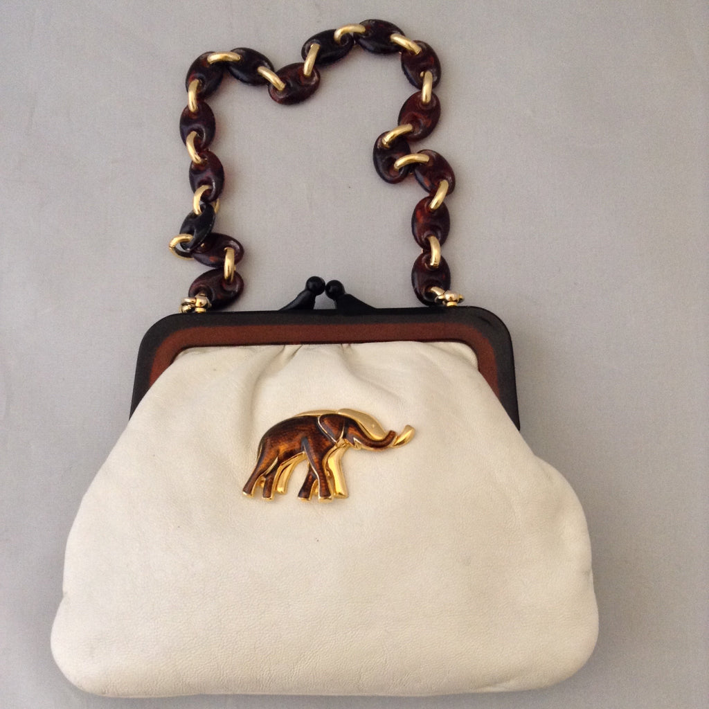 "Vintage purse with supple vanilla leather which complements the bold browns and golds of the strolling elephants adorning it. A tortoise and golden chain handle and lucite frame are so classic, creamy and dreamy. Dimensions - 6"" Height; 8"" Width; 15"" Length with chain"