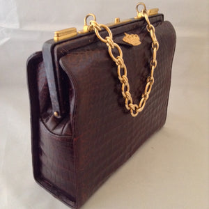 Vintage 1960s Nettie Rosenstein brown crocodile handbag with gold chain.