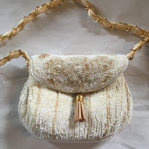 "Vintage purse micro-beaded in shades of pearl, ivory and gold. Lined in faux ostrich skin, this bag is perfect for bride, bridesmaid, flower girl or mother of the bride.  Dimensions - Height 4""; Width 5 1/2""; Handle 12""; Depth 2"""