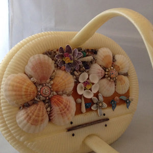 Vintage cream lucite basket purse with garden of seashells flowing the top.