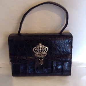 "The Suzanne Bag returns, this time in genuine black alligator with a unique antique silver crown closure.  You'll feel like the princess you are.  From the 1960's in pristine condition, this is a bag to treasure forever.  Dimensions - Height 5 3/4""; Width 7 1/2""; Handle 4""; Depth 3"""