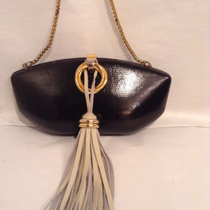 "Rare vintage bag by Italian maker RODO, this onyx-colored jewel can be carried as a clutch or worn with its long chain. The oversized leather tassel gives it that special sense of magic. Dimensions - Height 4""; Width 8""; Chain 22""; Depth 2 1/2"""