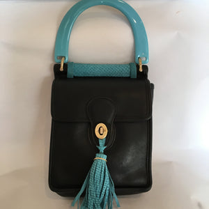 Formerly serious black Coach mailbag style purse becomes charming and witty with its exuberant teal handle and tassel. In the same contrasting color inside, the lining of genuine goat-skin is soft and supple as the gorgeous leather outside.