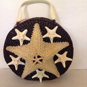 "This unusual round black straw bag with lucite handle and starfish motif will be noticed everywhere.  Wear it with a simple black or white sundress and strappy sandals.  No other accessory needed!  Dimensions - Body 9-1/2""; Diameter 3-1/2""; Handle - 3 1/2"""