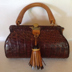 Original vintage brown crocodile purse with yellow leather handle, gussets and brown and black leather tassel make this vintage purse a true one-of-a-kind piece to carry everywhere.