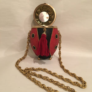 "Sparkly red, black and gold metallic with crystals and beading in all the right places. She opens to reveal a mirror perfectly placed for checking your lipstick! Dimensions - 6"" Height; 4"" Width; Chain Length 17"""