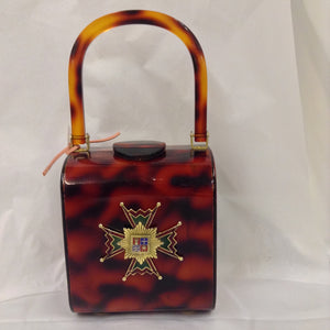 "A classic tortoise-colored lucite vintage purse with an impressive enamel antique Maltese cross. As roomy as it is stately.  In perfect condition, and made to last a lifetime, of course.  American, circa 1940  Dimensions - Height 6 1/4""; Width 5""; Depth 4""; Handle 6"""