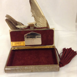 "Simple, bold and striking, this neutral colored lucite clutch features real feathers, a crimson suede tassel and sumptuous ruby red lining.  Dimensions - Height 5 1/2""; Width 8 1/4""; Handle 11 1/2""; Depth 1 3/8"""