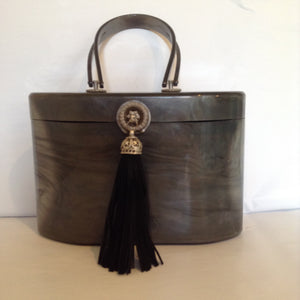 "1940s Wilardy lucite purse in swirls of grey. Black suede tassel, vintage medallion closure, lined in luscious peacock green, original mirror. Very unusual shape; sophisticated and collectable.  Dimensions - Height 6""; Width 8""; Depth 5""; Handle 4"""