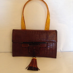 "Brown Leather Lovely. Vintage brown leather purse with lovely lucite closure and handle.  Bi-colored black and brown tassel.  Slim and elegant.  Dimensions - Height 5 1/2""; Width 9""; Handle 6 1/2""; Depth 1"""