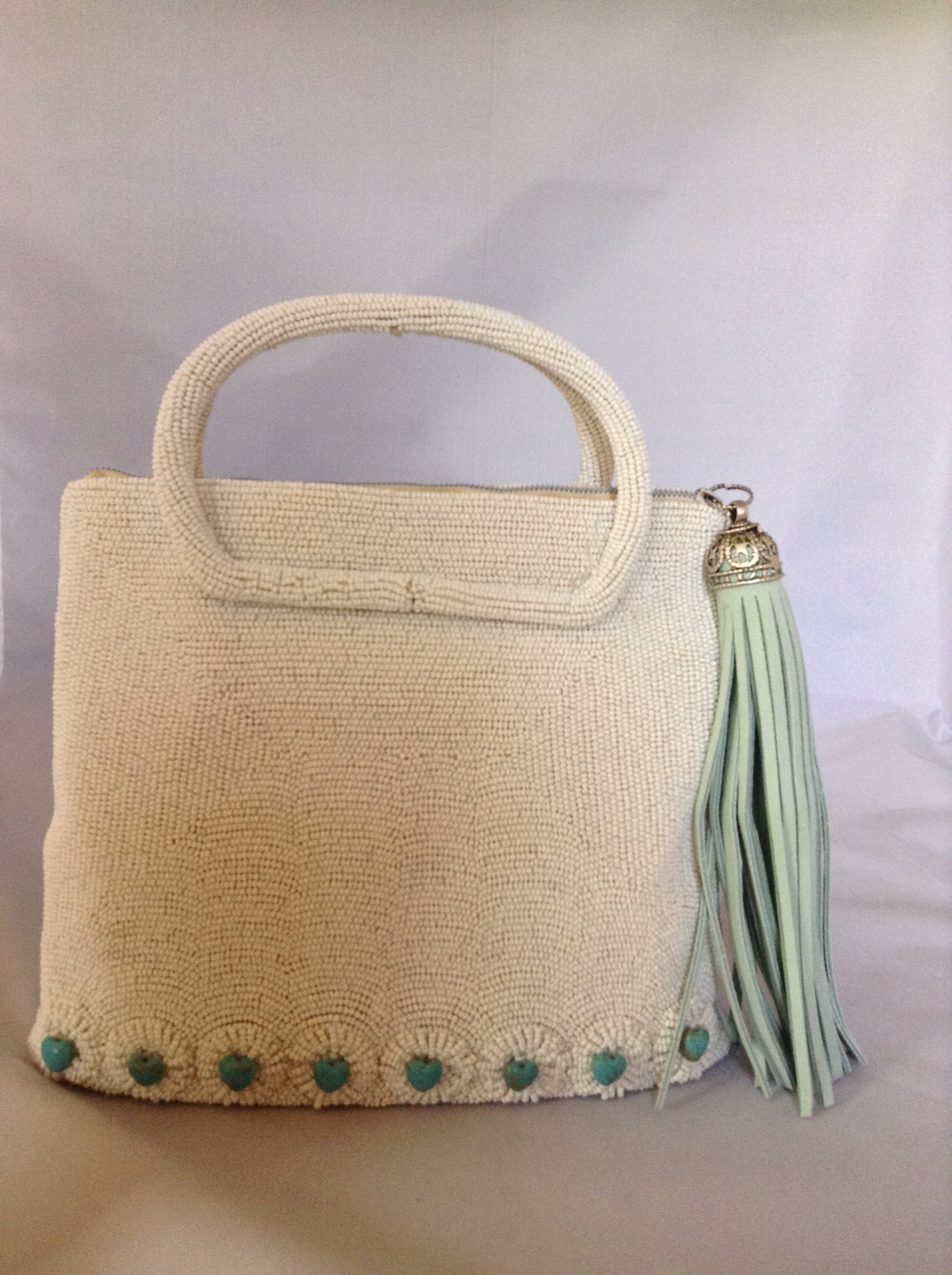 "42 genuine turquoise hearts adorn this 1950's vintage white beaded purse from Paris. With its original silk lining and aqua suede tassel you'll channel Audrey wherever you go.  Dimensions - 7.5""Height; 8"" Width; 3"" Depth; Handle 3"""