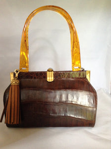 "Vintage brown alligator purse with amber lucite handles, original hardware, soft leather lining and an amber tassel combine to make this classic Spanish beauty your go-to purse forever.  Dimensions - Height 6.5""; Width 9""; Depth 4""; Handle 7"""