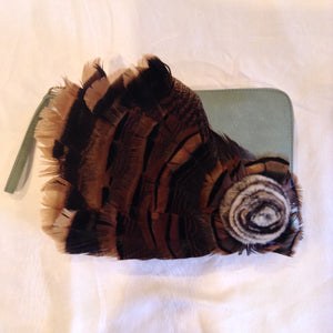 "Iridescent turkey feathers and a mink pom-pom adorn this luscious teal vegan vintage leather clutch. With its inside zipper pocket & handy leather wrist strap it will even hold your notebook computer.  Dimensions - Height 9""; Width 11""; Depth 1"""