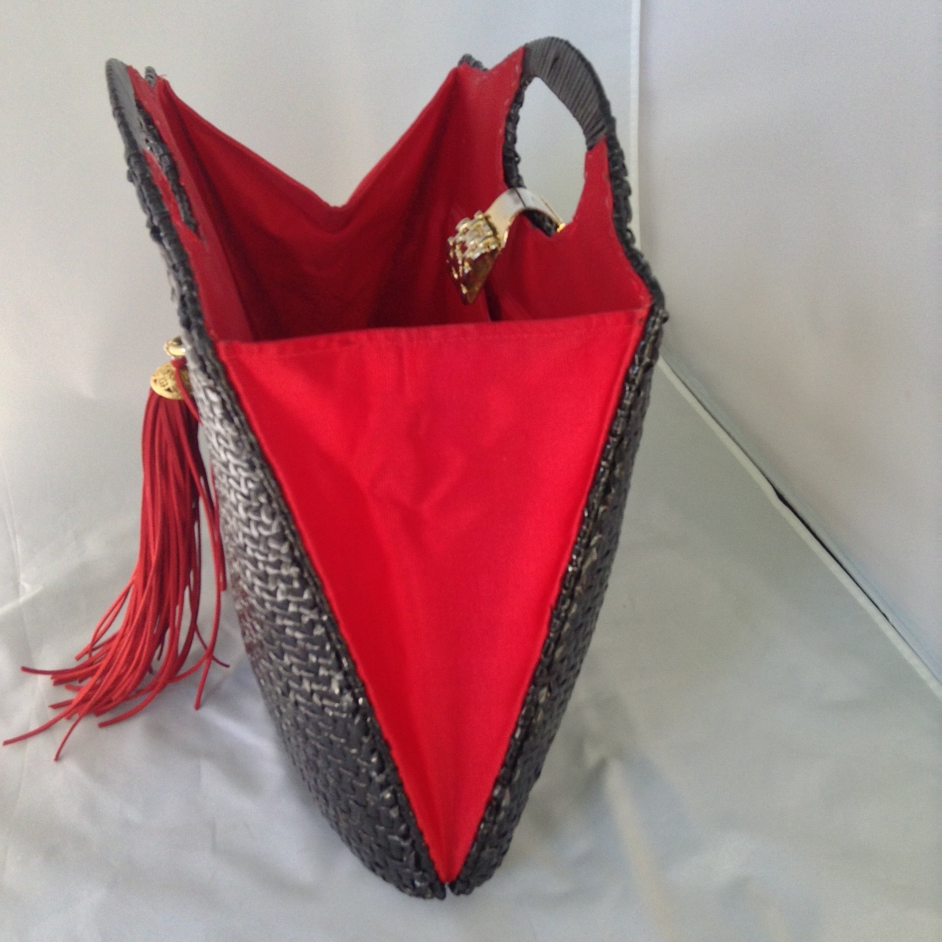 "Super cool black straw vintage bag from Neiman Marcus. Red silk lining, over-sized suede tassel, wonderful hardware. Makes a statement. All you need is the right hat. A big one. Audrey would approve.  Dimensions - Height 14""; Width 14""; Depth 3"""