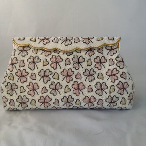 "This vintage cream micro-beaded clover leaf clutch was made in France in the 1940s. It's covered with delicate light pink and green clovers and pink hearts too. Finally, it has a gold trim brass scalloped top that drapes over it's original vintage brass frame. They must not celebrate St. Patty in France because this gorgeous bag has never been used, but you'll carry it all Spring!  Dimensions - Height 5.5""; Length 9.5""; Depth 2"""