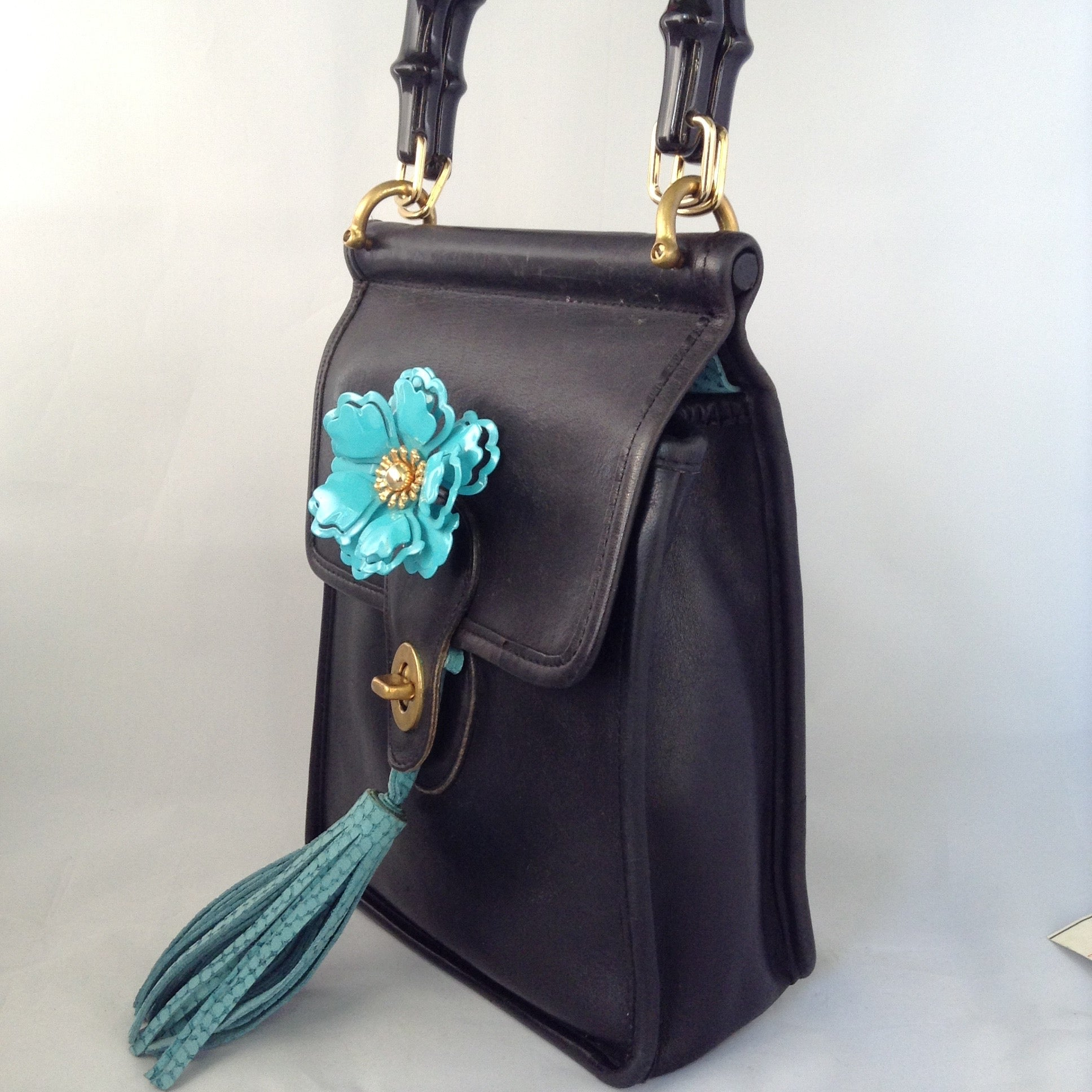 "Formerly a staid and serious Coach mailbag, this supple black glove leather vintage purse becomes witty and charming with its enamel flower and new teal suede tassel and lining.  Dimensions - Height 9""; Width 7""; Depth 3"""