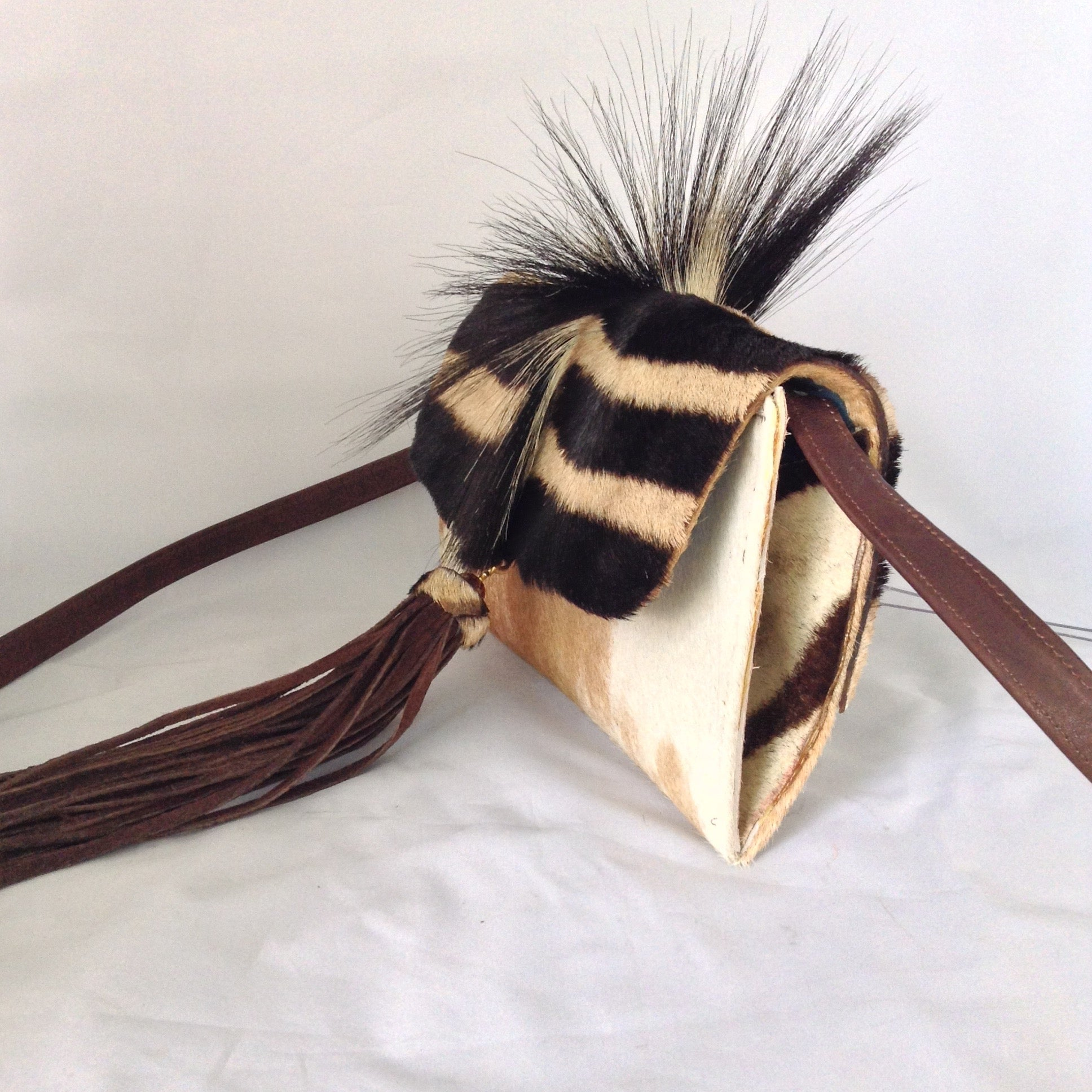 "Cow plus zebra adds up to a fabulous cross-body/clutch with attitude! This adorable vintage purse is made from real cowhide and African zebra pelt with mane, suede lining, fabulous suede tassel, detachable leather cross-body strap. What more could a girl want?  Dimensions - Height 6""; Width 10""; Depth 2"""