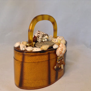 "Vintage Amber Lucite Oval Purse Topped With Multi-Colored Seashells And A Tiny Pelican Guarding Her Eggs. Mirror On Inside Top. Original Golden Brass Hardware. Dimensions - Height 3.75""; Width 7.5""; Depth 3.75""; Handle 3.25"""