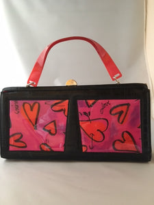 "Darling rectangular 1980's vintage purse with hand-painted hearts and a happy cherub wielding arrows. Black satin and vintage lucite handles complete the look.  Dimensions - Height 7""; Width 13-1/2""; Depth 3"""