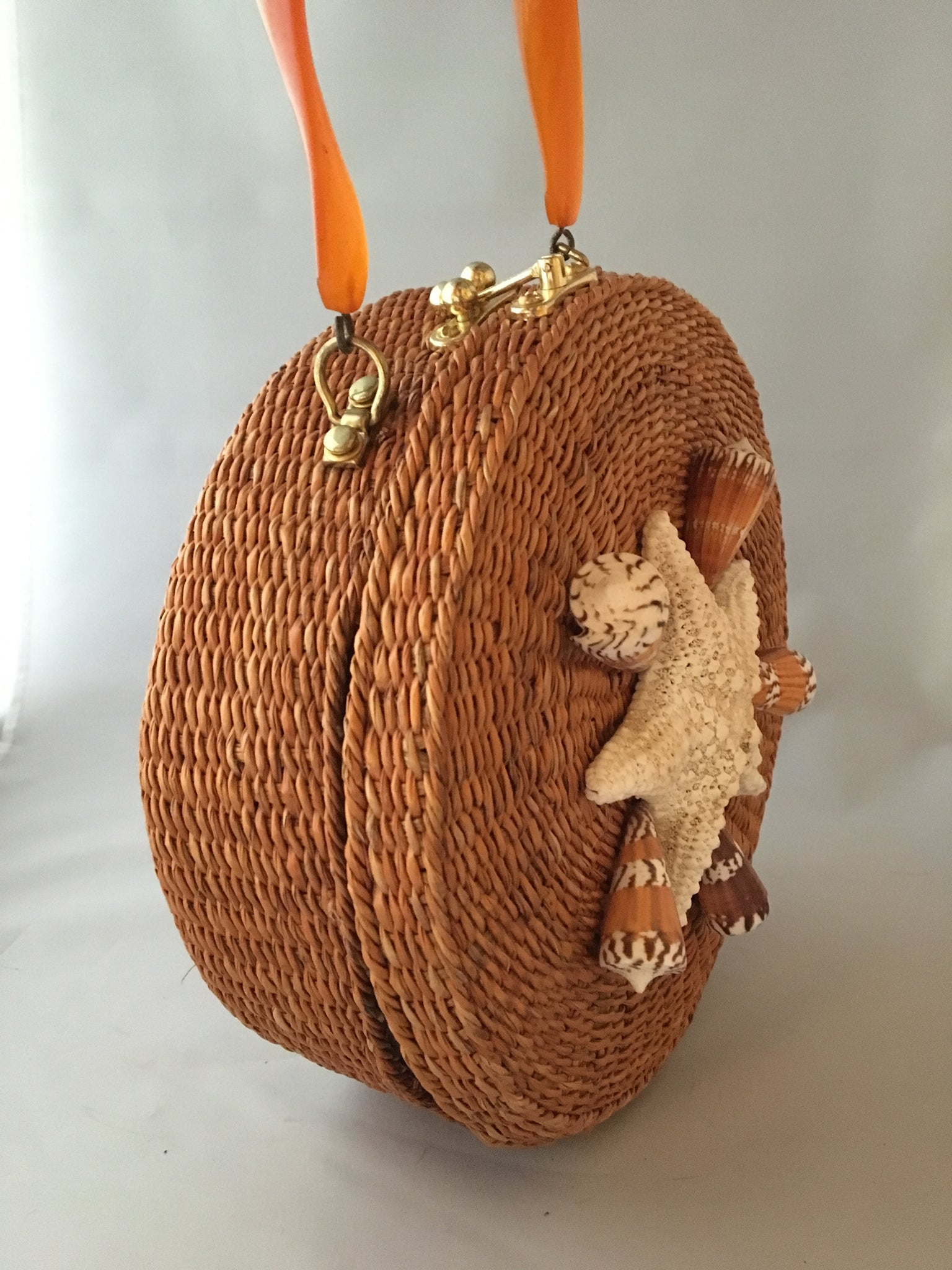"A great horned starfish and other wanna-bees encircle this unusual vintage straw bag. Leather lined with vintage lucite handle.You'll be in the inner circle wherever you take this!  Dimensions - Diameter 10""; Depth 4""; Handle 4"""