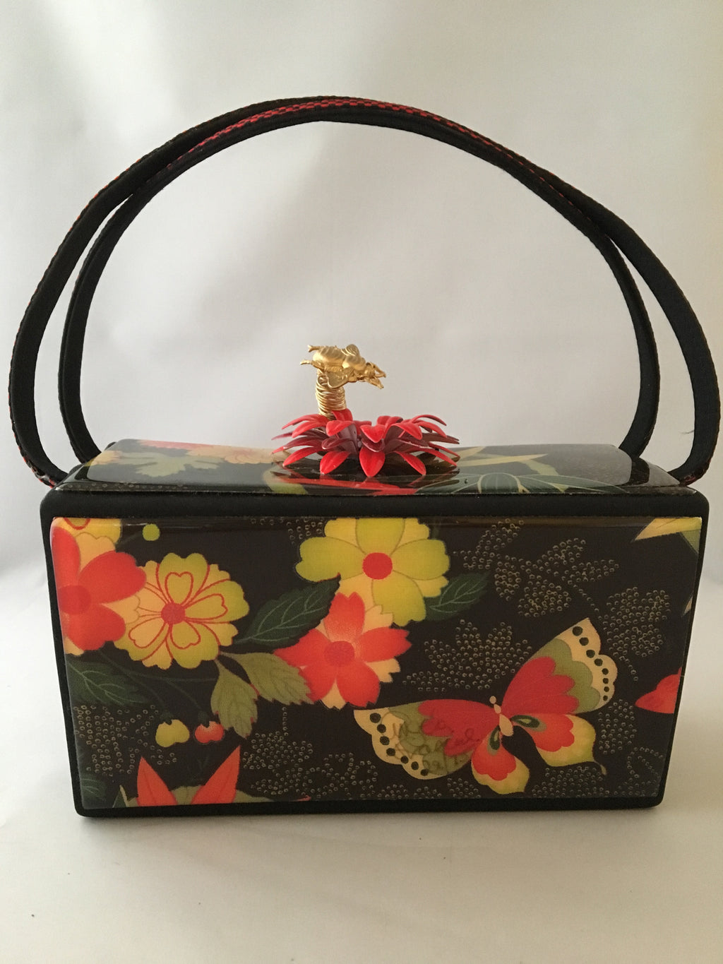 "Vintage box purse with flowers and butterflies. From its cheeky checkerboard handle to its vintage enamel daisy with bouncy pouncy bee, this brilliant handbag will take you from spring through fall. Included are a matching purse for your little girl and her dolly, too!  Dimensions - Height 4.5""; Width 7""; Depth 4.5""; Handle 6"""