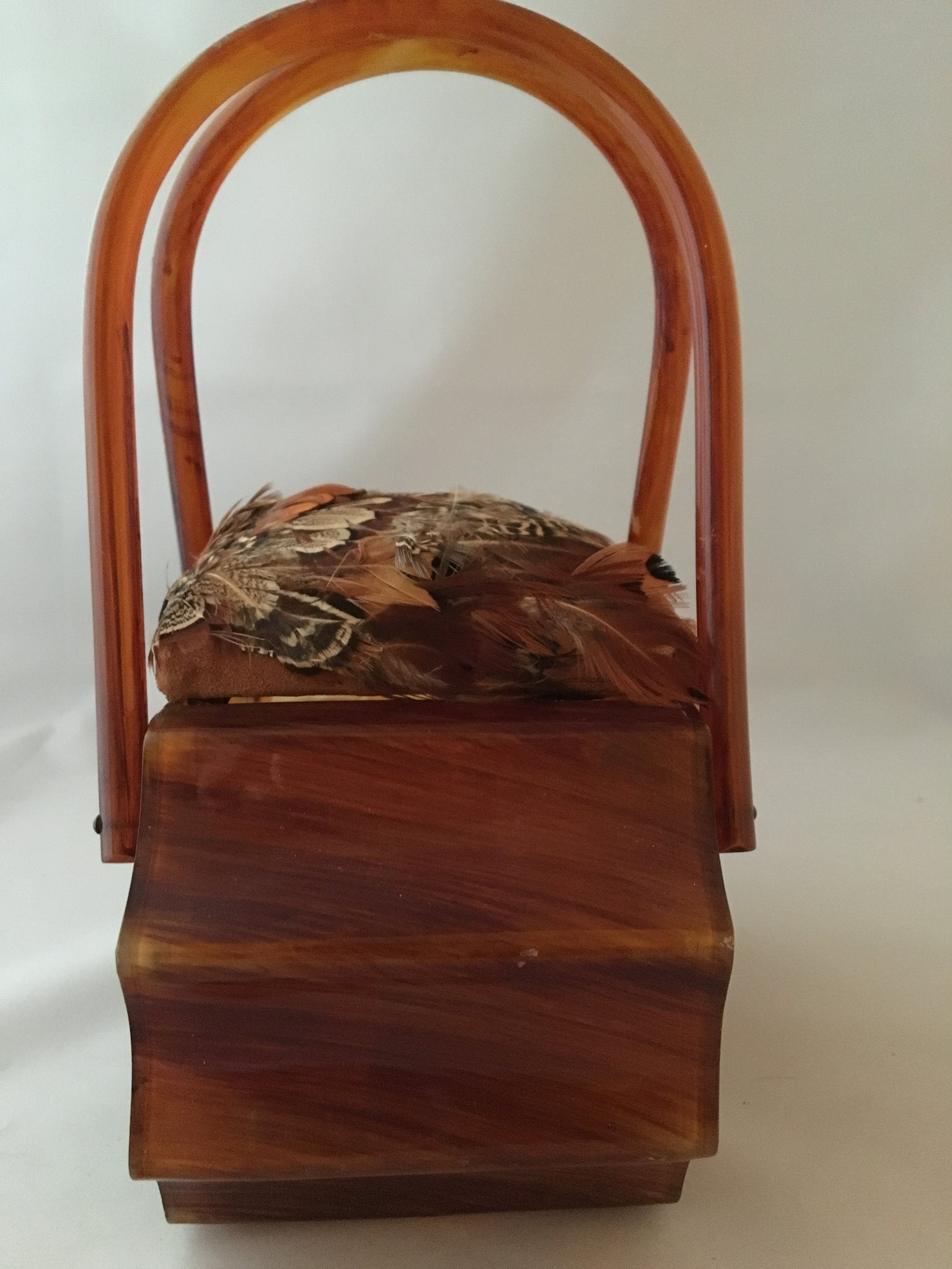 "Real pheasant feathers and a hand carved German folk-art pheasant adorn this 1940s vintage Wilardy lucite purse. Its unusual shape makes it a true collector's item. No other in the world is its equal.   Dimensions - Height 8""; Width 8""; Depth 4.5""; Handle 6"""