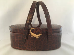 "Vintage lustrous brown alligator purse with a rare oval shape with double handle, leather-lined, original mirror in the top.  Dimensions - Height 9-1/2""; Length 4""; Width 4-1/2"""