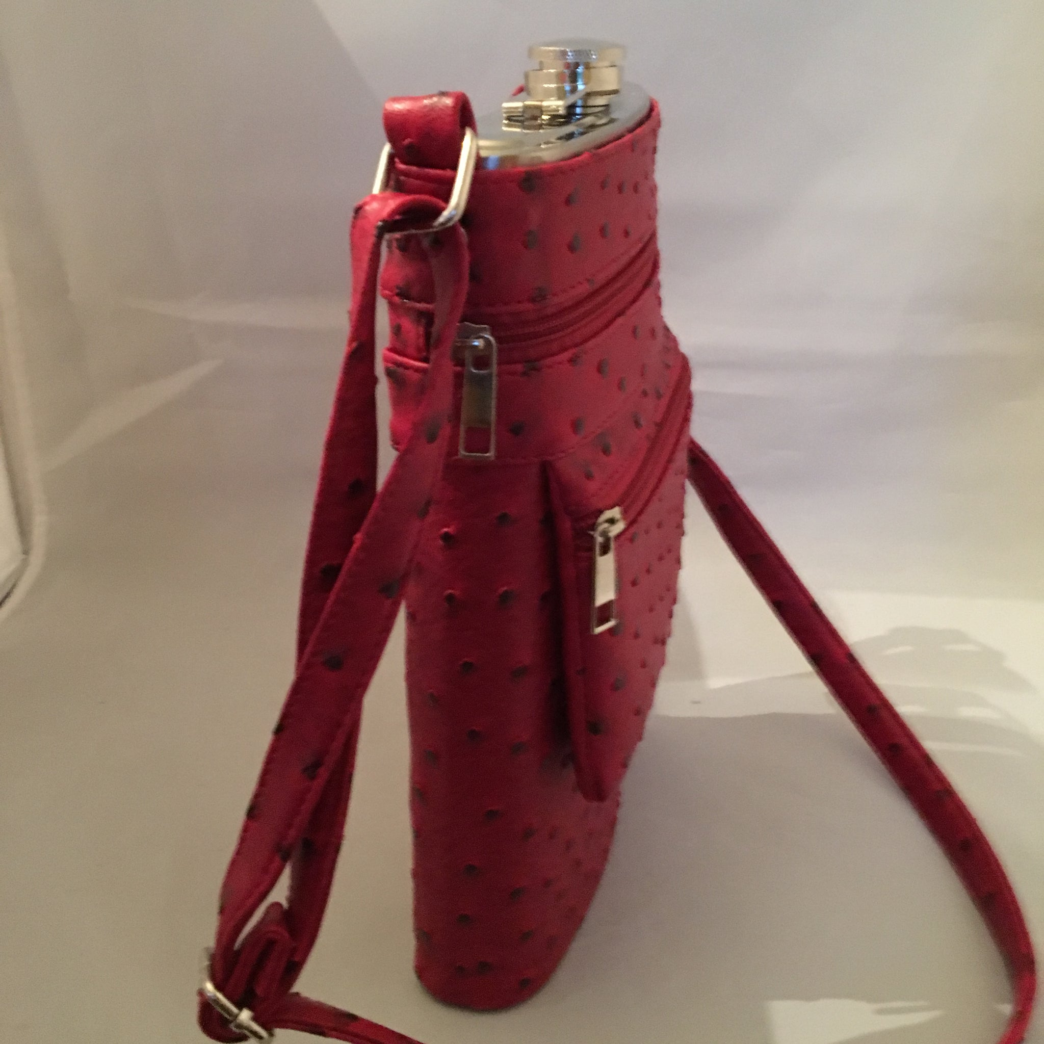 "This Ultimate Tailgate Flask discretely holds 2 bottles of wine! It's made of heavy-duty insulated aluminum, comes with its own funnel and sports a shoulder strap. You'll be the hit of the parking lot! Check to see if we have it in your school colors!  Dimensions - Height 12""; Width 7""; Depth 2"""