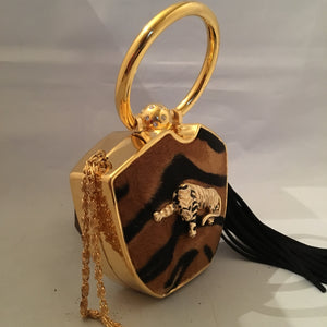 Darling yet daring, this vintage solid brass box purse roars attitude! Plush faux tiger pelt, golden tiger pendant, long black tassel, hideaway shoulder chain make it a conversation piece-de-resistance!