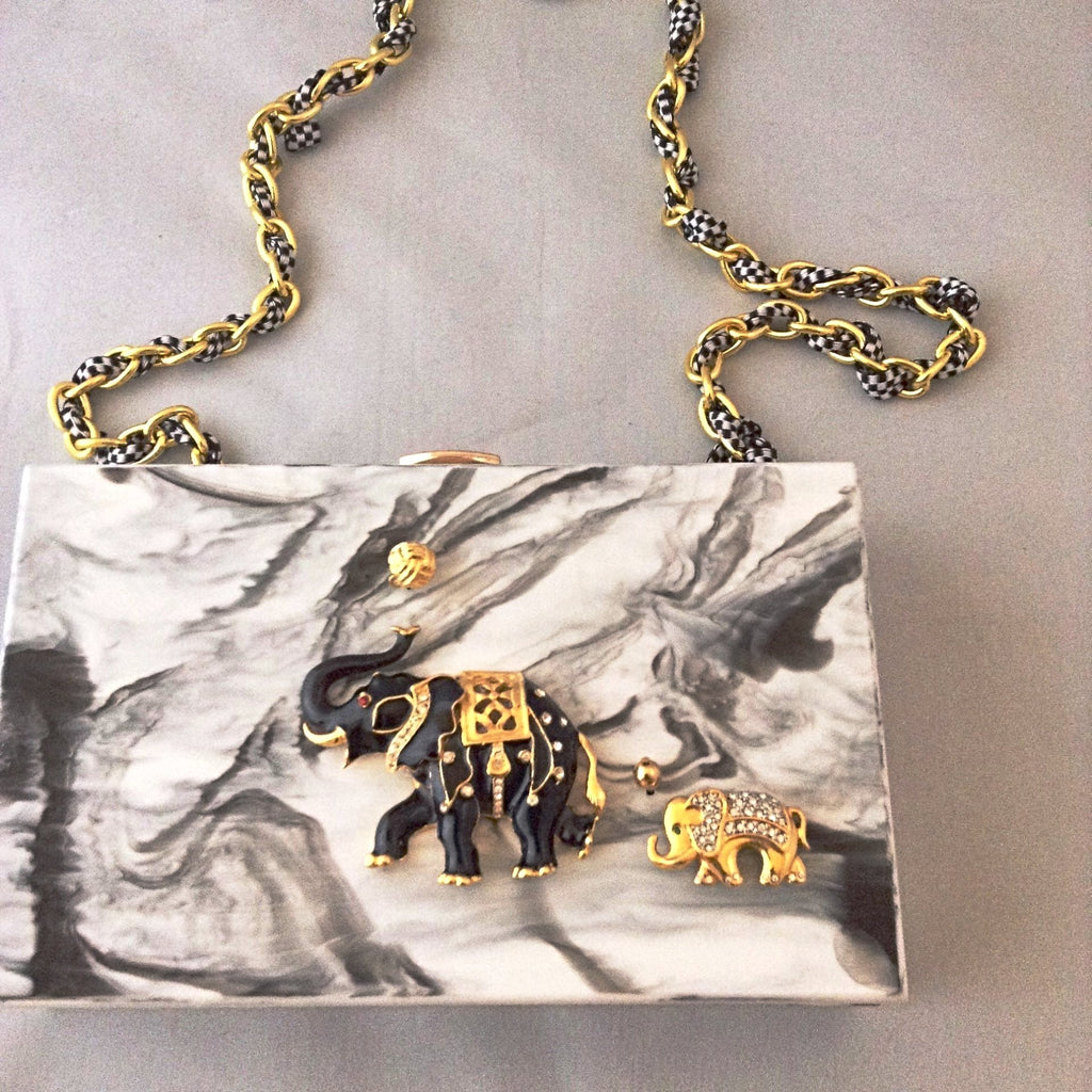 A fabulous box clutch or cross body bag with mama and baby enamel elephants, perfect for lunch to evening - or to a political rally! The hidden chain adds a whimsical touch of fun!
