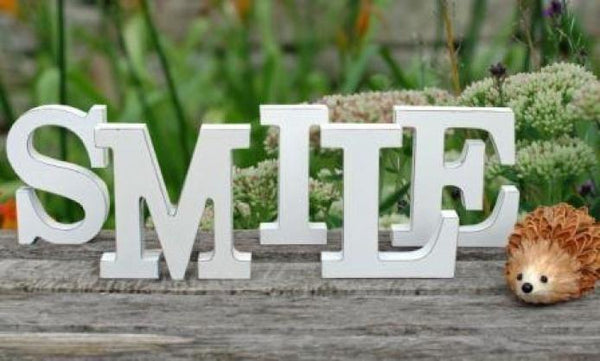 Smile in white wooden letters
