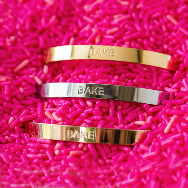 "Bake Cuff - Gold bracelet with the engraved word ""Bake"""