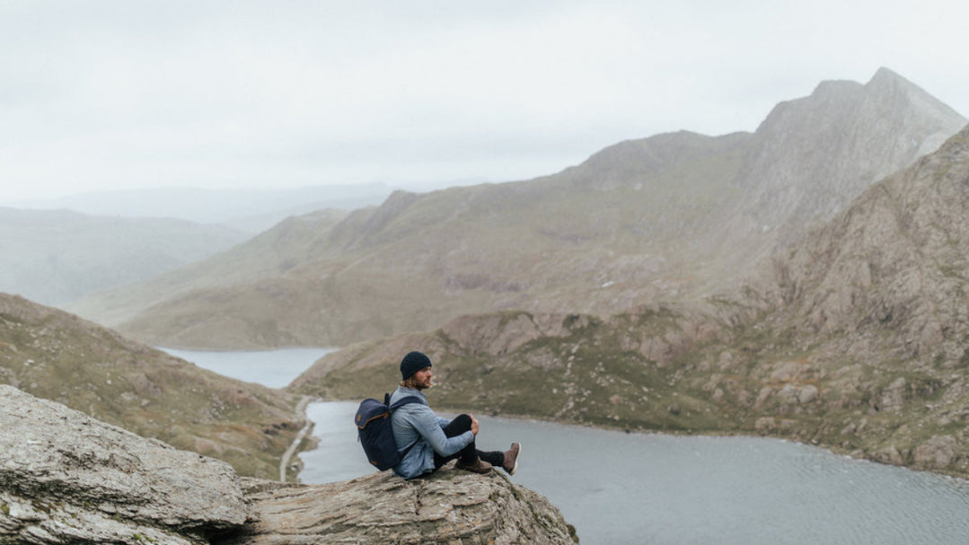 Man sat on rock above snowdon with Stubble & Co Navy Backpack on